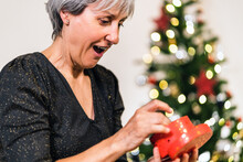 Side View Of Excited Mature Female In Elegant Dress Opening Box And Enjoying Gift During Christmas Celebration At Home