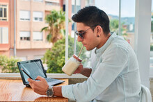 Side View Of Young Stylish Male Freelancer Using Smartphone And Drinking Milkshake While Working Remotely On Laptop In Cafe