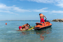 Unrecognizable Male Coworkers In Life Vests On Motor Boat Helping Guy On Sea During Training Under Blue Cloudy Sky