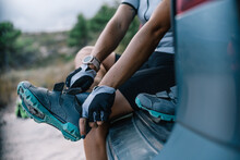 Cropped Unrecognizable Female Bicyclist In Helmet And Sunglasses Sitting In Trunk Of Car And Preparing For Ride While Putting On Boots And Looking At Camera