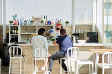 Back View Of Unrecognizable Male Clients Sitting At Counter In Summer Cafe While Barman In Mask And Gloves Preparing Healthy Refreshing Smoothies
