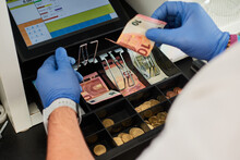 From Above Of Crop Anonymous Male Cashier In Protective Gloves Putting Banknotes Into Money Box During Work