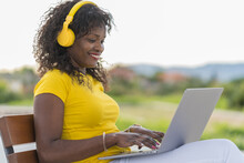 Side View Of Delighted African American Self Employed Woman In Headphones Sitting On Bench On Street And Typing On Netbook While Working On Remote Project