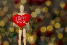 Wooden Dummy Holding Red Heart Written I Love You, With Blurred Background Of Balls And Hearts.