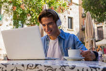Overjoyed Young Male In Wireless Headphones Getting Incredible News On Laptop And Celebrating Victory While Sitting At Table With Cup Of Coffee On Cafe Terrace