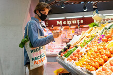 Young Male Customer In Protective Mask Carrying Eco Friendly Recycled Fabric Shopping Bag And Choosing Fresh Groceries While Taking Picture On Smartphone Buying Food In Supermarket