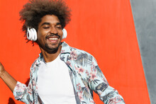 Young Masculine Bearded African American Male With Afro Hairstyle And Closed Eyes Listening To Music In Headphones Near Red Wall In Town