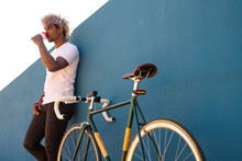 Black Man And Afro Biker Drinking Takeaway Coffee On A Blue Wall. Black Biker Concept. Take Away Coffee.