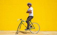 Afro Black Man Doing A Trick With His Bike. Black Biker Concept. Black Cyclist On A Yellow Background.
