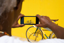 Black Man Taking A Photo Of His Bike With The Phone On A Yellow Background. Concept Of Selling Online. Sell A Bicycle.