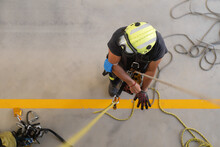 From Above Of Unrecognizable Firefighter In Bright Protective Helmet Putting On Heat Resistant Gloves Near Stretched Ropes During Routine Practices