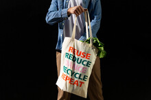 Crop Anonymous Male Buyer Holding Fabric Shopping Bag With Text Message Of Reuse And Recycle Concept On Black Background