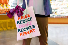 Crop Anonymous Male Buyer Holding Fabric Shopping Bag With Text Message Of Reuse And Recycle Concept While Making Purchases In Supermarket
