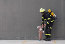 Firefighter In Striped Uniform And Hardhat With Extinguisher Touching Fire Hydrant While Standing Near Cement Wall On Pavement During Routine Practices