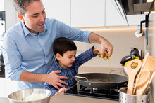 Glad Young Father Teaching Adorable Little Son To Cook While Pouring Oil In Pan Together In Modern Light Kitchen