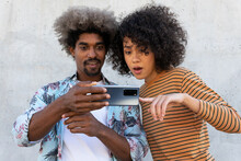 Smiling Stylish Black Man Near Surprised Ethnic Female Partner With Afro Hairstyle Pointing With Finger At Cellphone On Street
