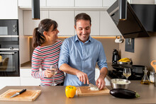 Happy Smiling Couple In Casual Clothes Standing Near Kitchen Counter And Cutting Onion While Cooking Lunch Together