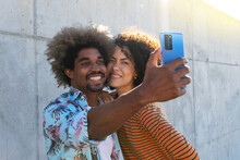 Content Multiracial Couple Of Friends With Afro Hairstyle Taking Selfie On Cellphone While Embracing Near Wall In Sunlight In Back Lit