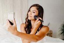 Smiling Young Brunette Wearing White Shirt Applying Blush On Cheek While Using Mobile Phone Screen As Mirror In Cozy Bedroom