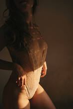 Side View Of Cropped Unrecognizable Curvy Female Wearing Lace Bodysuit Standing In Room Lit By Sunlight