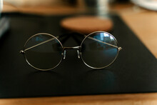 Classic Eyeglasses Of Round Shaped Placed On Black Mat On Blurred Wooden Desk