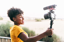 Cheerful Young African American Female Blogger Holding Selfie Stick With Camera And Recording Video For Vlog While Standing On Terrace Against Blurred Nature During Summer Travel