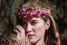 Charming Romantic Young Long Haired Female With Pink Floral Wreath Standing Near Spruce Branches And Looking At Camera