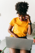 High Angle Of Modern Young Black Female Freelancer Answering Phone Call And Browsing Laptop While Working On Remote Project At Home