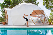 Side View Of Anonymous Barefoot Male Standing In Natarajasana Pose Near Swimming Pool And Tent While Practicing Yoga