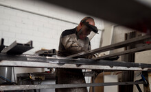Serious Male Worker In Dirty Apron Standing At Workbench And Preparing Metal Details For Welding