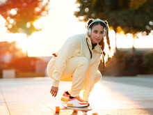 Full Body Of Positive Young Ethnic Lady In Stylish Sportswear Riding Longboard And Listening To Music In Headphones In Park At Sunset