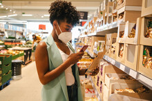 Modern Young Black Woman In Protective Mask Using App On Mobile Phone For Checking Information About Product While Making Purchases In Supermarket