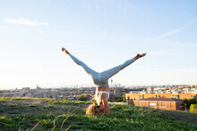 Full Body Faceless Slim Female In Sportswear Performing Headstand With Legs Outstretched While Practicing Yoga On Lush Hilltop Against City Landscape