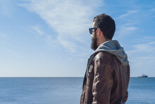 Side View Of Pensive Ethnic Bearded Male Traveler In Trendy Clothes And Sunglasses Relaxing On Rocky Beach Of Sea In Seven Sisters