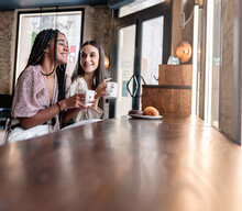 Side View Of Cheerful Young Multiracial Women In Trendy Outfits Drinking Coffee And Chatting Happily While Spending Time Together In Modern Cafeteria