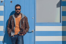 Confident Young Bearded Ethnic Male In Stylish Outfit And Sunglasses Standing Near Blue Door With Hands In Pockets While Resting In Seven Sister On Sunny Day