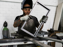Busy Male Welder Wearing Dirty Protective Gloves And Apron Standing At Workbench With Metal Frame And Working In Grunge Garage