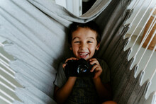 From Above Laughing Boy Holding Modern Professional Photo Camera While Resting On Hanging Hammock In Apartment And Looking At Camera Happily