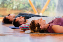 Side View Of People With Closed Eyes Lying On Mats After Practicing Yoga On Wooden Floor In Class