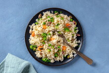 Vegan Rice With Vegetables, Healthy And Delicious, The Plate Is Shot From Above On A Blue Background