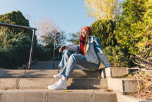 Portrait Of A Black Girl With Colored Braids Sitting On A Staircase. Dressed With A Vintage Denim Jacket And A Red Head Scarf. Urban Style.