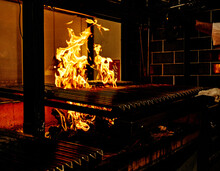 Professional Metal Grill With Burning Fire For Traditional Barbecue Preparation In Modern Restaurant Kitchen