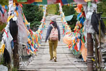 Young Ethnic Female Tourist In Warm Clothing And Crossing Simple Long Narrow Suspension Wooden Bridge Decorated With Bright Multi Colored Pieces Of Fabric In Daylight