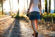 Back View Of Crop Anonymous Female Traveler In Casual Outfit Walking On Pathway In Park With Photo Camera In Hand At Sunset