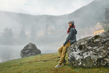 Full Body Side View Of Female Traveler Admiring Majestic View Of Calm Cuoka Lake Located Near Tibetan Buddhist Temple Among Mountains Covered With Dense Forest