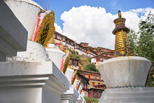 From Below Of Vibrant Blue Sky With Clouds Over Small Red Houses And Golden Monuments On Pedestals