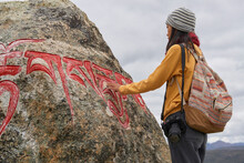 Full Body Side View Of Female Tourist In Warm Clothing And Hat Looking At Large Stone With Om Mani Padme Hum Mantra On Surface In Village Of Baiyu In China