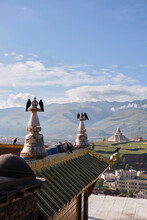 White Stone Monument Near Vast Green Foggy Mountain With Sacred Tibetan Temple In Ganzi City In Sichuan Province