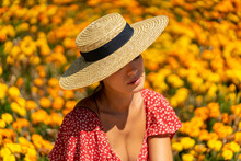 Delighted Female Wearing Summer Dress And Stylish Straw Hat Sitting On Stone Border Of Flowerbed In Park While Resting During Weekend On Sunny Day