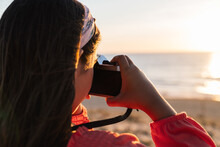 Back View Of Anonymous Stylish Teen Girl In Casual Clothes Standing On Sandy Beach And Taking Photo Of Sunset Over Ocean